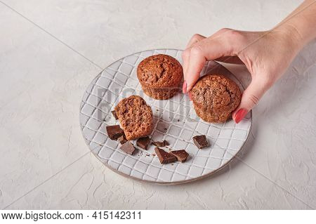 Womans Hand Holds A Cupcake, Other And Pieces Of Chocolate In Textured Plate On Wooden Light Backgro