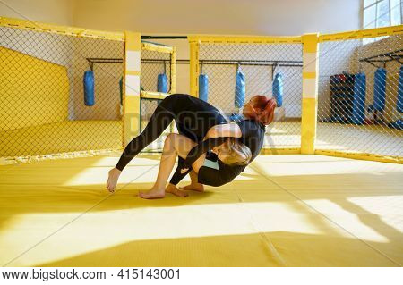 Female MMA fighter performs throw through herself