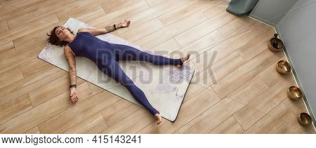 Young Girl Resting After A Hard Work-outing At Home On A Sports Mat. Girl Lying On The Sport Mat Nex