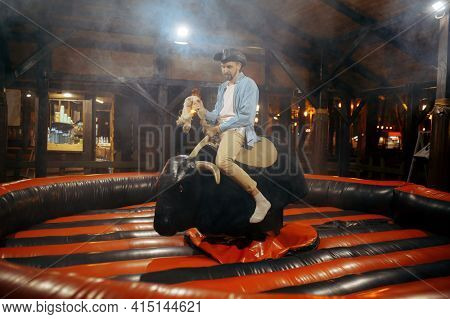 Man on rodeo attraction in night amusement park