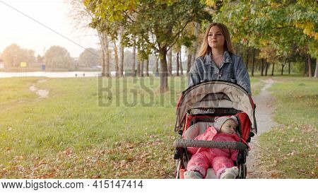 A Young Mother With A Stroller Walks In The Autumn Evening.