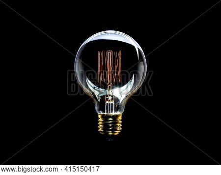 Incandescent Glass Lamp On Black Background With Glare