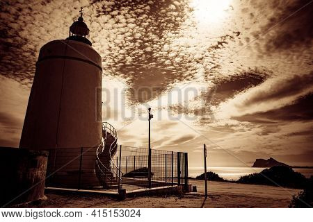 Carbonera Lighthouse Located On Punta Mala And Gibraltar Rock In Distance. La Alcaidesa, Spain. Lant