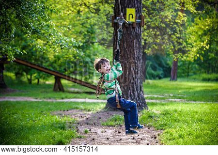 Smiling Boy Rides A Zip Line. Happy Child On The Zip Line. The Kid Passes The Rope Obstacle Course