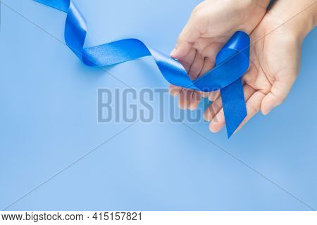 Hands Holding Deep Blue Ribbon On Blue Background With Copy Space. Colorectal Cancer Awareness Colon
