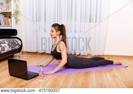 Attractive Sporty Woman Practices Yoga Asana At Home. Woman Exercising At Home In Front Of Her Lapto