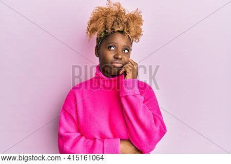 Young african woman with afro hair wearing casual winter sweater thinking concentrated about doubt with finger on chin and looking up wondering