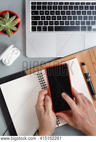 Man Writing In Agenda And Using Cell Phone On A Grey Office Desk Top View. Business Concept