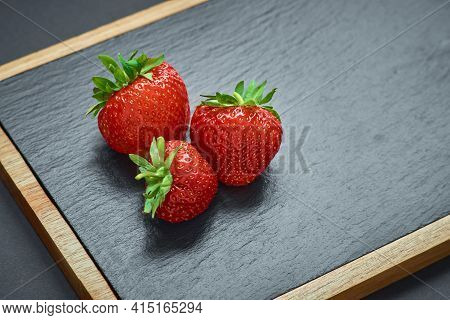 Strawberries On Black Stone Board. Berries In The Kitchen
