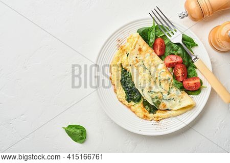 Omelet Or Omelette With Spinach, Cherry Tomato And Pepper Seasoning On A White Plate, On White Backg