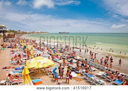 COSTINESTI, ROMANIA - AUGUST 8: Crowded beach with tourists in summer on August 8, 2012 in Costinesti, Romania. Costinesti is a famous summer destination for hundred of thousands of tourists a year.