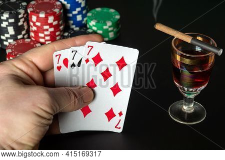 Poker Cards Three Of A Kind Or Set Combination. Close Up Of A Gambler Hand Is Holding Playing Cards