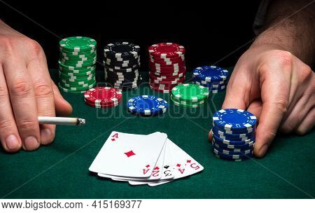 Hands Of A Gambler Closeup And Chips On Green Table In A Poker Club. A Player Places A Bet On A Winn