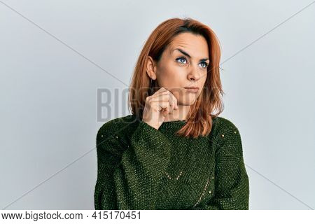 Hispanic young woman wearing casual winter sweater thinking concentrated about doubt with finger on chin and looking up wondering