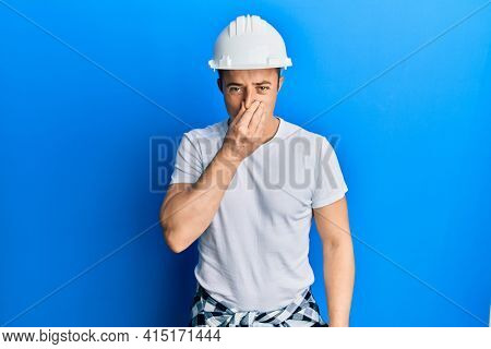 Handsome young man wearing builder uniform and hardhat smelling something stinky and disgusting, intolerable smell, holding breath with fingers on nose. bad smell