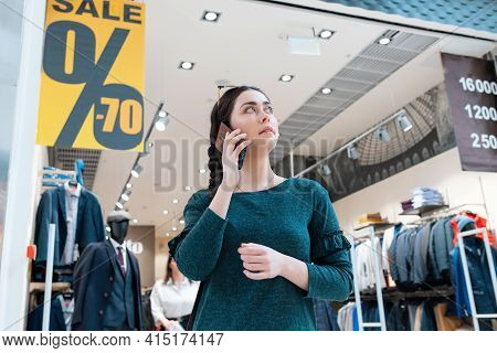 A Young Woman Call On The Phone. In The Background, There Is A Store And Posters With A Sale. Bottom