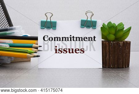 Commitment Issues - Words On A White Sheet With Clamps Against The Background Of A Cactus And Jars W