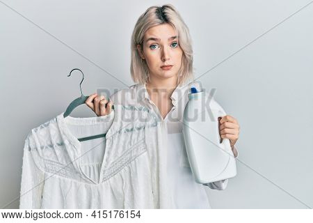 Young blonde girl holding detergent bottle and shirt skeptic and nervous, frowning upset because of problem. negative person.