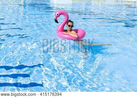 Summer Sale. Young Sexy Woman In Bikini Swimsuit, Sunglasses With Pink Flamingo Relaxing In Blue Poo