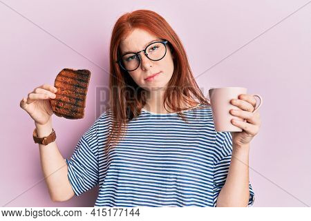 Young red head girl holding burned toast for breakfast skeptic and nervous, frowning upset because of problem. negative person.