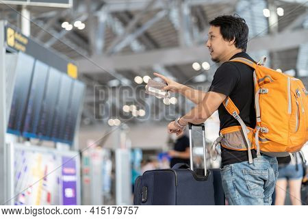 Portrait Of Asian Traveler With Luggage With Passport Looking And Pointing Over The Flight Board For