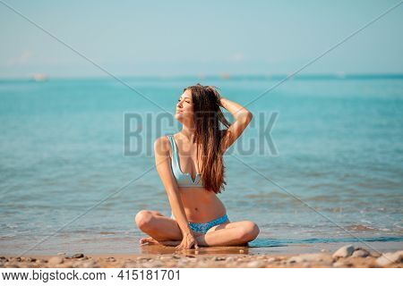 Sunbathing. A Pretty Young Woman Sitting Crossed Legs On The Ocean And Posing. The Concept Of Summer