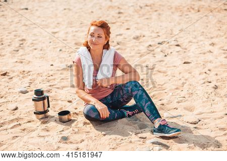 After Training. Smiling Adult Woman In Sports Clothes, Sitting On The Sand. Next To It Is A Bottle O