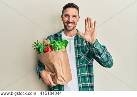 Handsome man with beard holding paper bag with groceries waiving saying hello happy and smiling, friendly welcome gesture