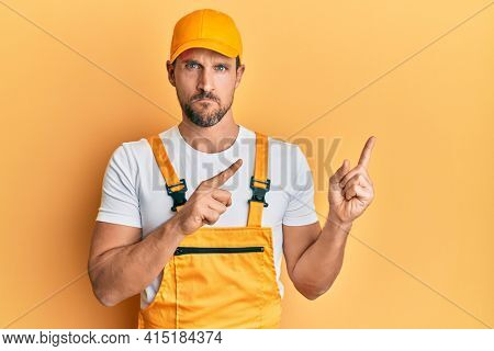 Young handsome man wearing handyman uniform pointing to the side skeptic and nervous, frowning upset because of problem. negative person.