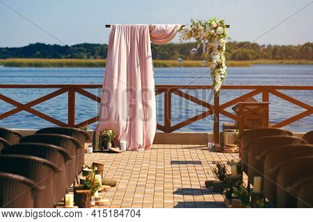 A Wedding Decorated Arch On The River Bank Against The Backdrop Of A Sunset. Wedding Day And Prepara