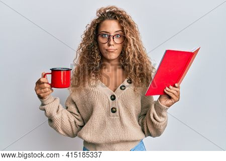 Beautiful caucasian teenager girl reading a book and drinking a cup of coffee skeptic and nervous, frowning upset because of problem. negative person.