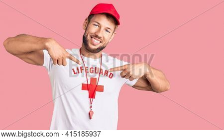 Young caucasian man wearing lifeguard t shirt holding whistle looking confident with smile on face, pointing oneself with fingers proud and happy.