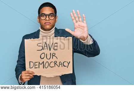Young handsome hispanic man holding save our democracy protest banner with open hand doing stop sign with serious and confident expression, defense gesture