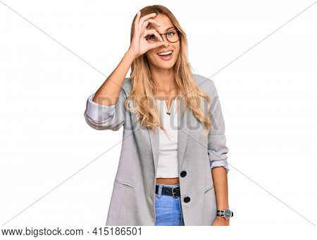 Beautiful blonde young woman wearing business clothes doing ok gesture with hand smiling, eye looking through fingers with happy face.