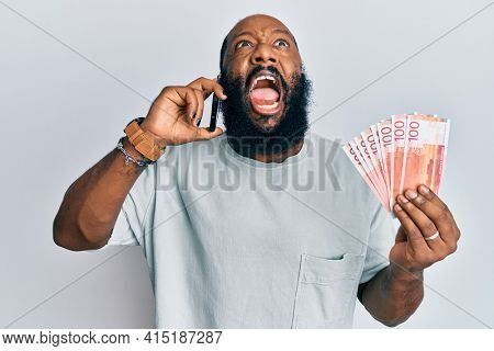 Young african american man having conversation talking on the smartphone holding norwegian krona banknotes angry and mad screaming frustrated and furious, shouting with anger looking up.