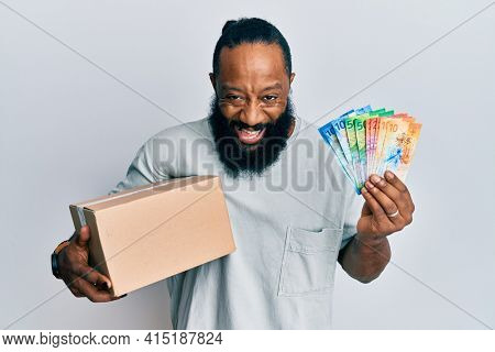 Young african american man holding delivery box and swiss franc banknotes smiling and laughing hard out loud because funny crazy joke.
