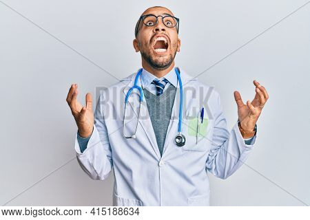 Hispanic adult man wearing doctor uniform and stethoscope crazy and mad shouting and yelling with aggressive expression and arms raised. frustration concept.