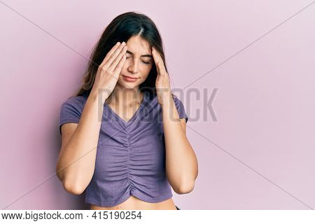 Young caucasian woman wearing casual clothes with hand on head for pain in head because stress. suffering migraine.