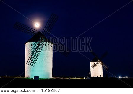 The Historic White Windmills Of La Mancha Above The Town Of Campo De Criptana At Night Under A Full