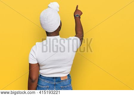 Young african woman with turban wearing hair turban over isolated background posing backwards pointing ahead with finger hand