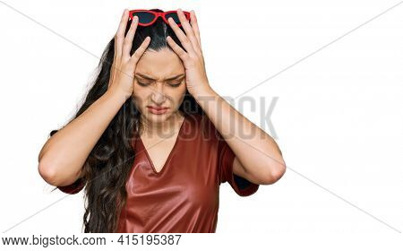 Brunette young woman wearing dress and sunglasses suffering from headache desperate and stressed because pain and migraine. hands on head.