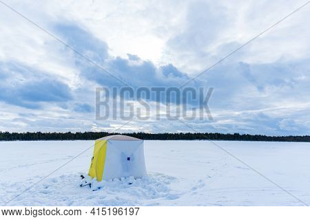 Tent Camping On Ice Of The River During Ice Fishing. Ice Fishing Adventures Concept In Winter Time.