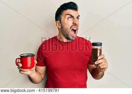 Young hispanic man holding cup of soluble coffee angry and mad screaming frustrated and furious, shouting with anger looking up.