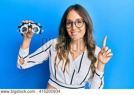 Young brunette woman holding optometry glasses smiling with an idea or question pointing finger with happy face, number one