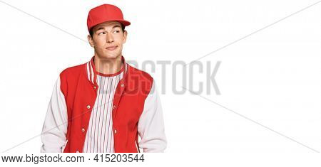Handsome caucasian man wearing baseball uniform smiling looking to the side and staring away thinking.