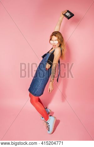 Retro Style Fashionable Woman With Vintage Video Cassette On Pink Background
