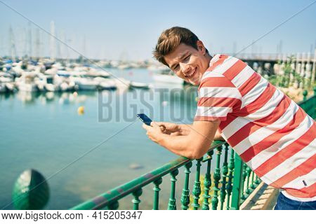 Young caucasian man smiling happy using smartphone leaning on the balustrade at the river.