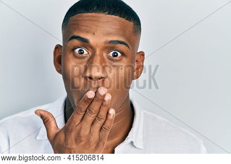 Young black man over isolated background covering mouth with hand, shocked and afraid for mistake. surprised expression
