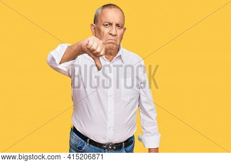 Handsome senior man wearing elegant white shirt looking unhappy and angry showing rejection and negative with thumbs down gesture. bad expression.