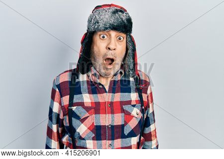 Handsome mature man wearing winter hat with ear flaps scared and amazed with open mouth for surprise, disbelief face